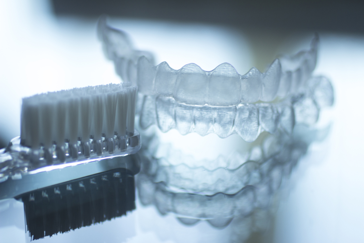 Invisible dental teeth brackets tooth aligners plastic braces retainers to straighten teeth and toothbrush dental hygien care. Orthodontic temporary removable straighteners in dental office dentists surgery clinic.Artistic color photo in creative blue tones.